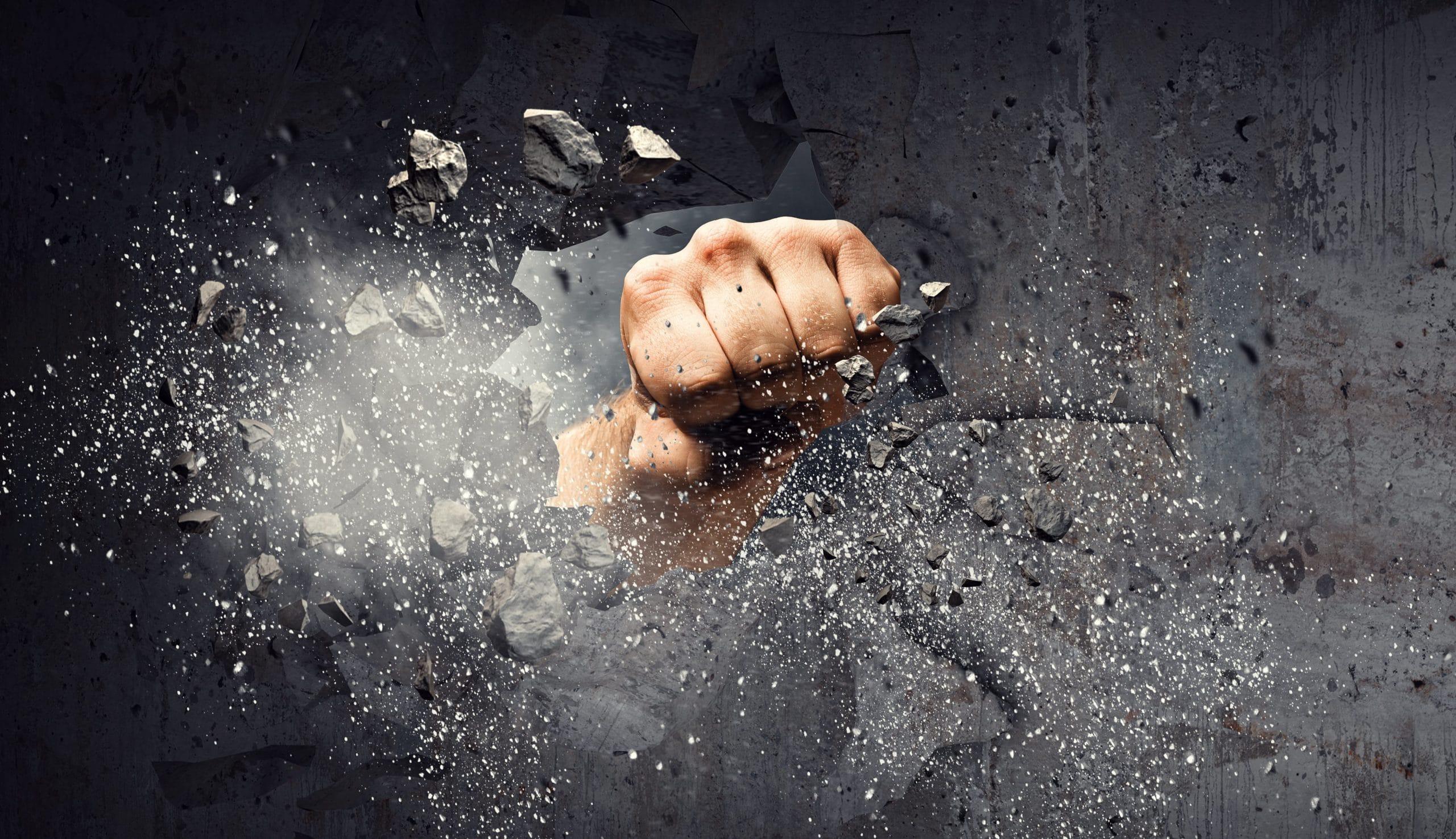 Eine Faust bohrt ein Loch in eine Betonwand